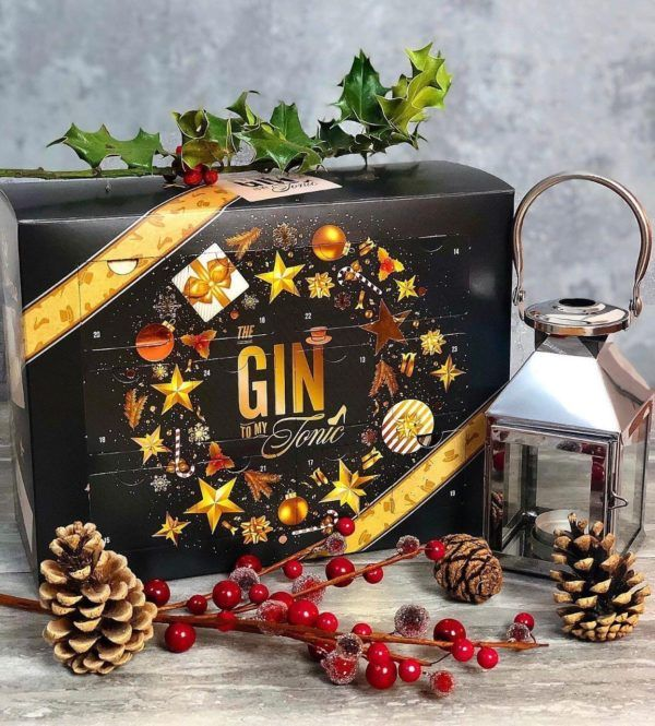 The Gin To My Tonic Christmas Advent Calendar with festive accessories on a sparkly background