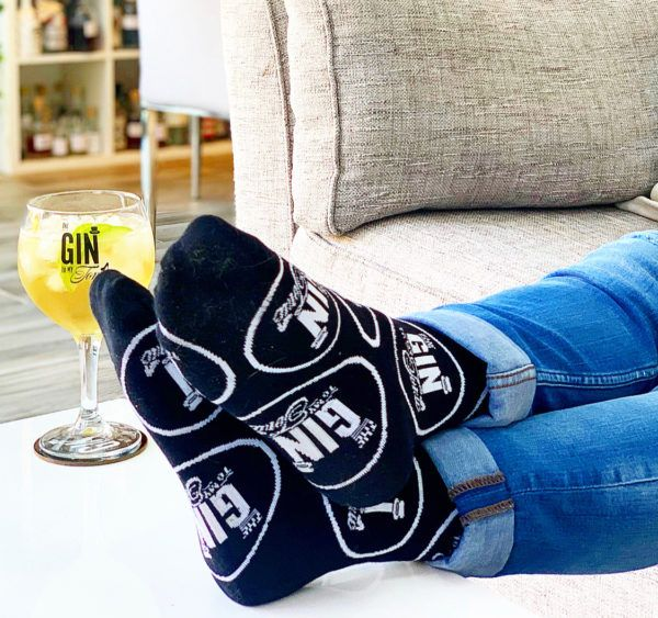 The Gin To My Tonic Socks worn on feet resting on the table with gin copa glass in the background