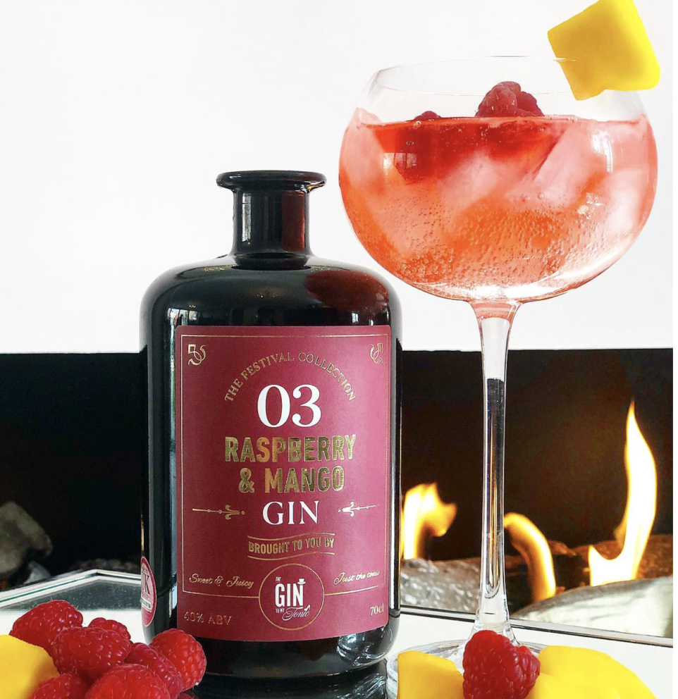Raspberry & Mango Gin bottle with gin and tonic infront of fireplace with garnishes of rasperries and mango beside it
