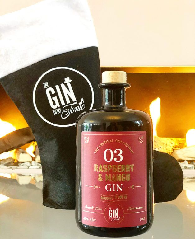 The Gin To My Tonic Raspberry and Mango Gin from The Festival Collection with a branded Gin Stocking infront of A Fireplace