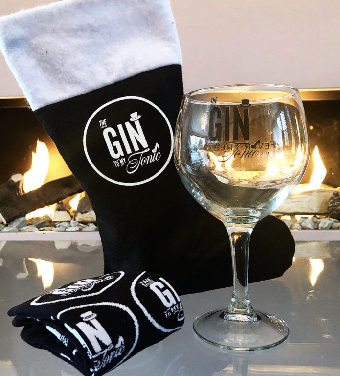 The Gin To My Tonic Stocking infront of a fire with branded socks and copa glass