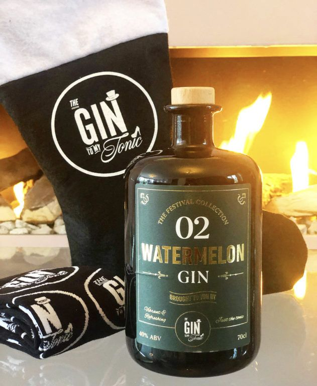 The Gin To My Tonic Watermelon Gin with branded stocking and socks in front of a fireplace